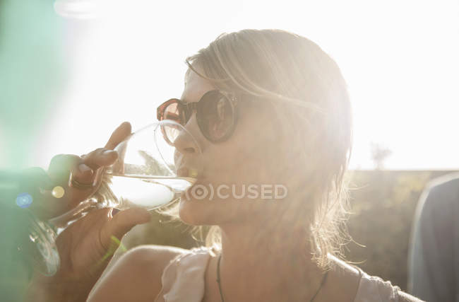 Head and shoulders of young woman wearing sunglasses drinking from wine glass looking away — Stock Photo