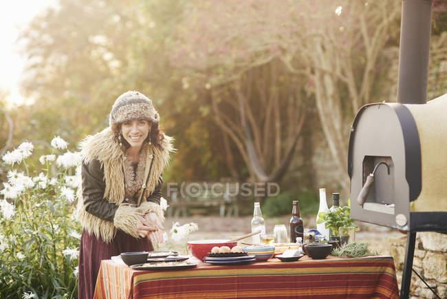 Mature hippy female preparing food on garden table — Stock Photo