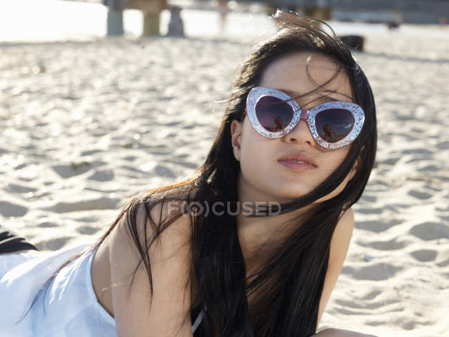 db3c748bc1 Portrait of young woman on beach in funky sunglasses