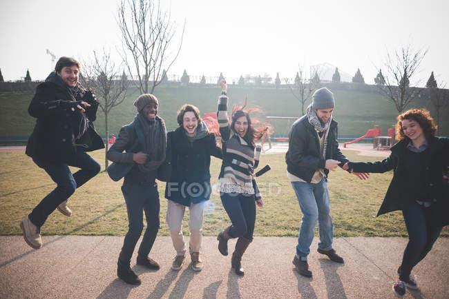 Sei giovani adulti amici ballando e saltando nel parco — Foto stock