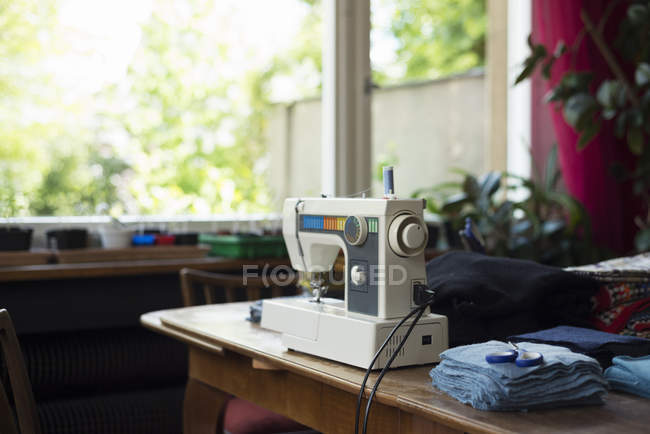 Sewing machine on table with fabric and scissors — Stock Photo