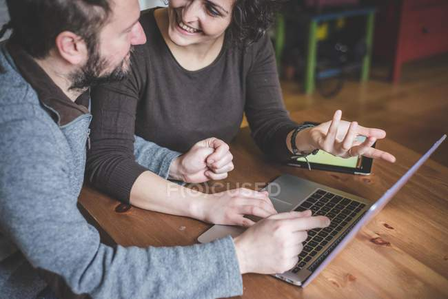 Couple sitting at table, using laptop — Stock Photo