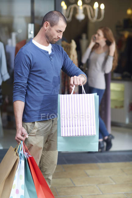 Young woman shopping, man outside holding bags, looking at watch — Stock Photo