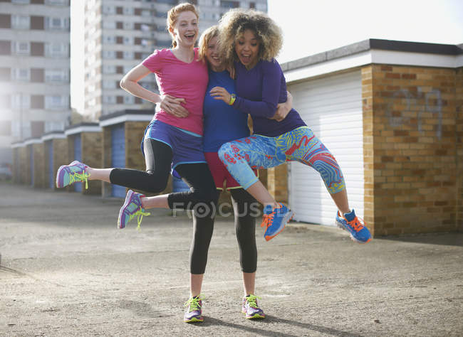 Portrait of three women wearing sports clothing jumping — Stock Photo