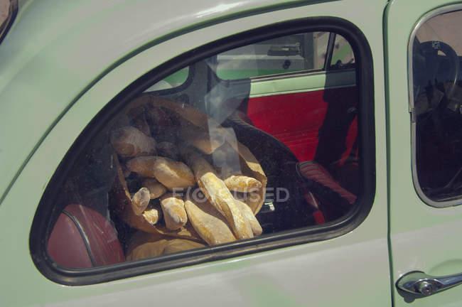 Bolsas de baguettes en asiento trasero del coche de época, Brignogan, Francia - foto de stock