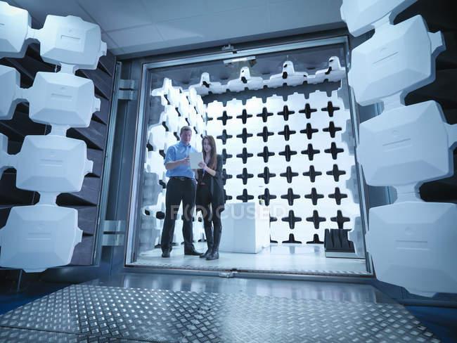 Инженеры, проверяющие результаты испытаний в лаборатории в анехоической камере, используемой для электромагнитного тестирования совместимости электрического и электронного оборудования — стоковое фото