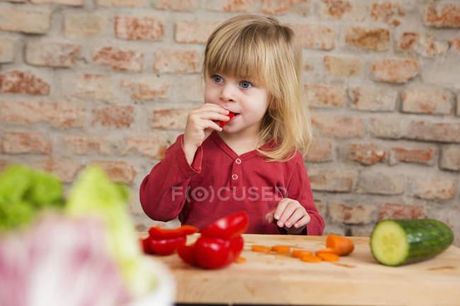 Мила дівчина малюка в кухні їдять сирі овочі — стокове фото