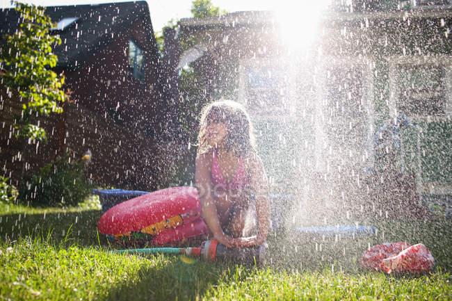 Jeune fille jouant dans arroseur de jardin — Photo de stock
