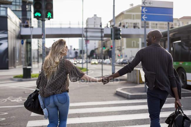 Vista posteriore della donna caucasica a piedi e uomo di etnia africana in strada, coppia innamorata portando il bagaglio e tenendosi per mano, pedoni che attraversano la strada — Foto stock