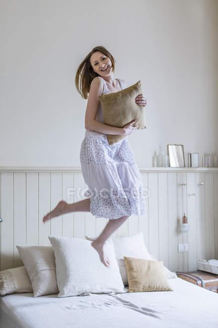 Женщина в белом платье прыгает на кровати и смотрит в камеру улыбаясь. — стоковое фото