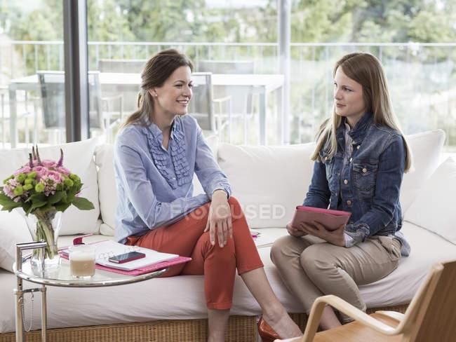 Молодая деловая женщина берет интервью у взрослой женщины на диване — стоковое фото