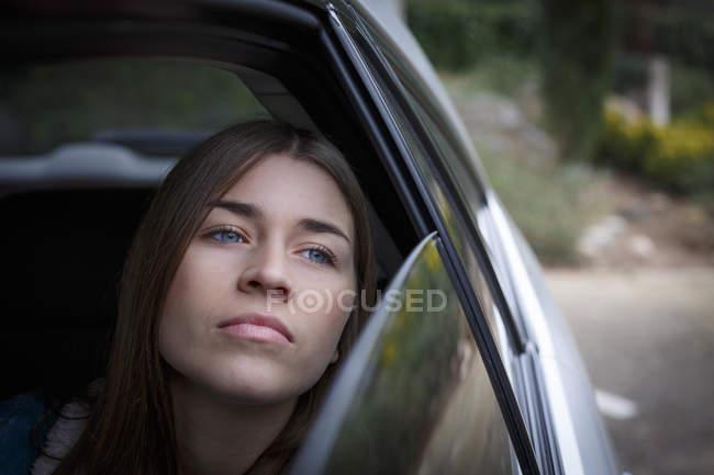 Mujer joven mirando hacia atrás a través de la ventana interior del coche - foto de stock