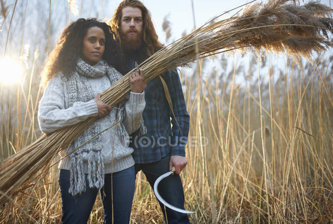 Couple harvesting wheat with scythe — Stock Photo
