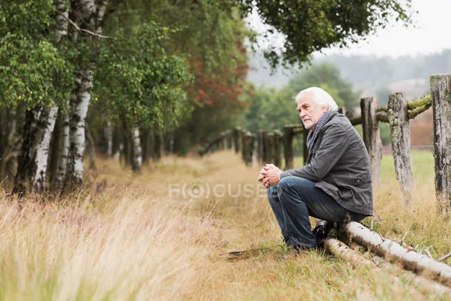 Homem sênior sentado no log — Fotografia de Stock