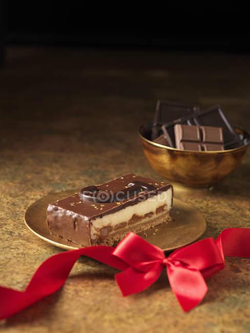 Tranche de dessert au chocolat avec ruban rouge — Photo de stock