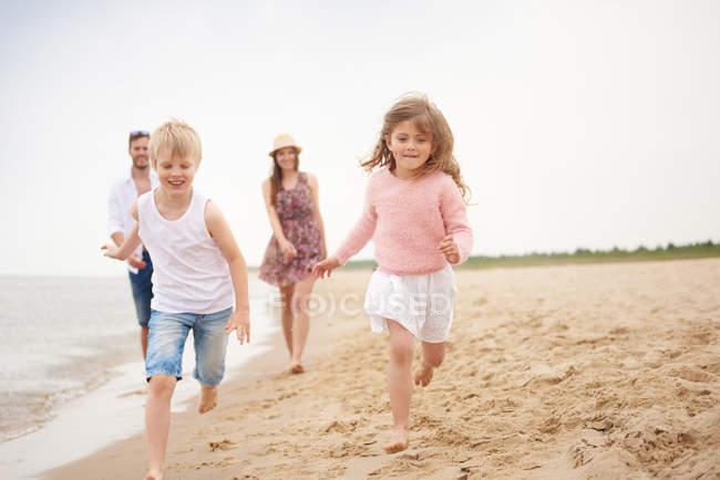 Famille courant le long de la plage de sable fin — Photo de stock