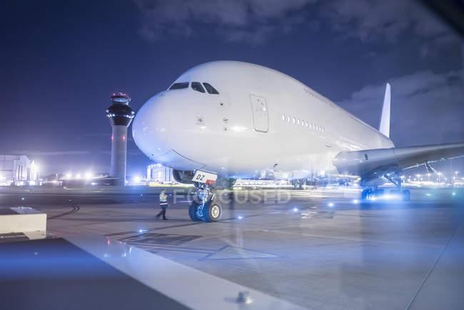 Engenheiro que comunica com piloto de aeronaves A380 na pista à noite — Fotografia de Stock