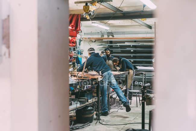 Metalwork team working in forge workshop — Stock Photo