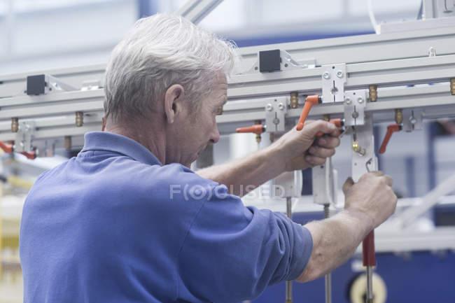 Ingénieur travaillant sur rail métallique dans une usine d'ingénierie — Photo de stock