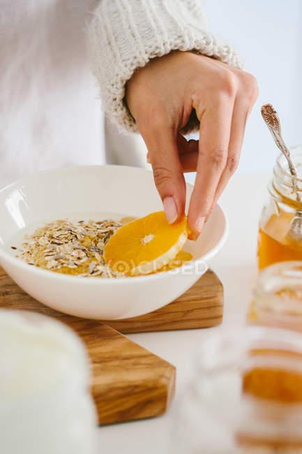 Cropped image of woman adding orange to muesli for breakfast — Stock Photo