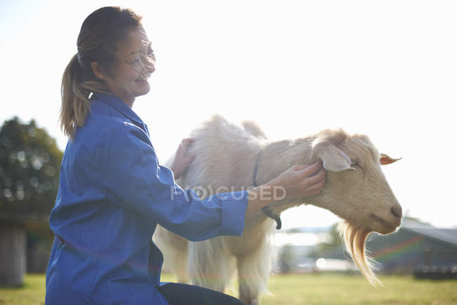 Farm worker tending to goats on farm — Stock Photo