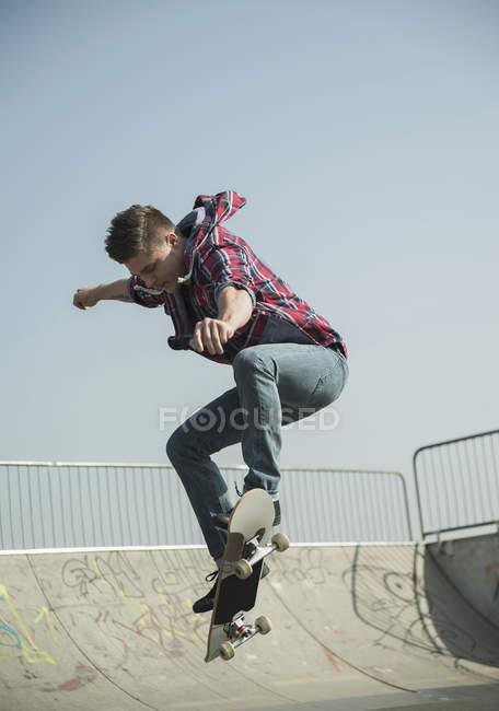 Jeune homme faisant le tour de planche à roulettes — Photo de stock