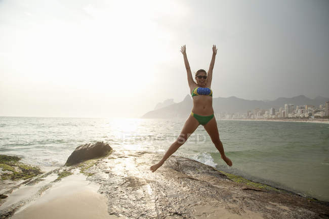 Young woman wearing bikini jumping mid air on  Ipanema beach, Rio De Janeiro, Brazil — Stock Photo