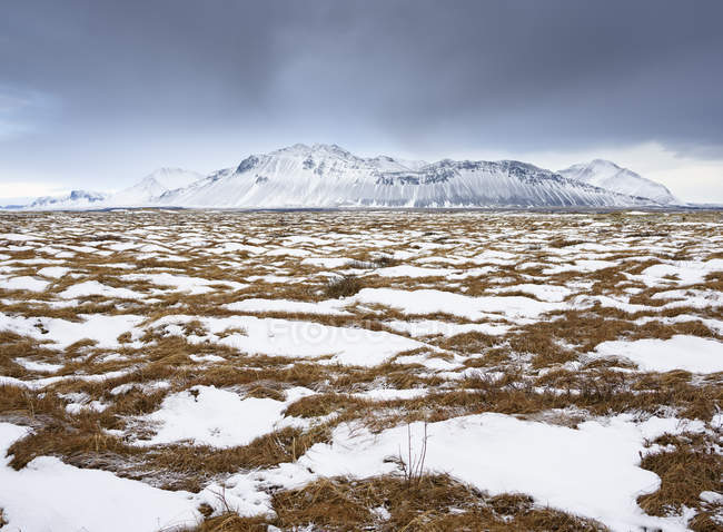 Snowcapped valley and rocky mountains under cloudy sky — Stock Photo