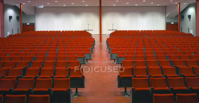 Righe di sedie rosse nella sala vuota — Foto stock