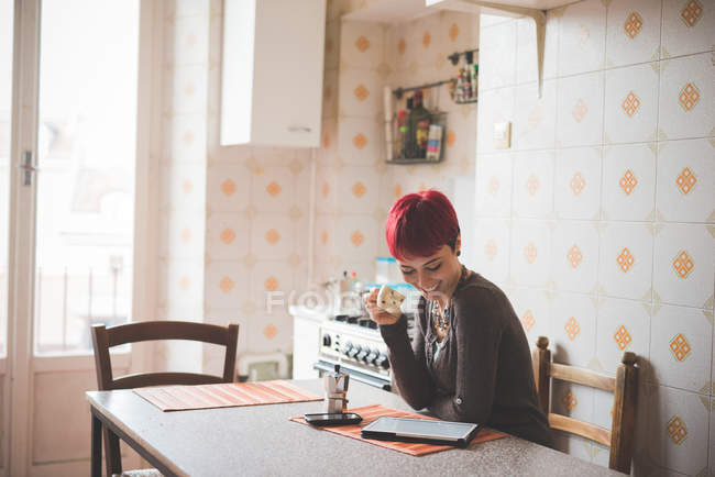 Young woman sitting at table drinking coffee, looking at digital tablet — Stock Photo