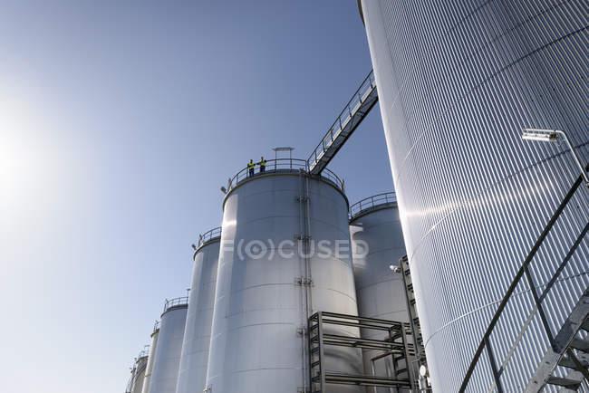 Trabajador en la parte superior de los tanques de almacenamiento en fábrica de mezcla de aceite - foto de stock