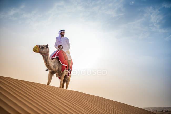 Mann trägt traditionelle Naher Osten Kleidung Reiten Kamel in der Wüste, Dubai, Vereinigte Arabische Emirate — Stockfoto