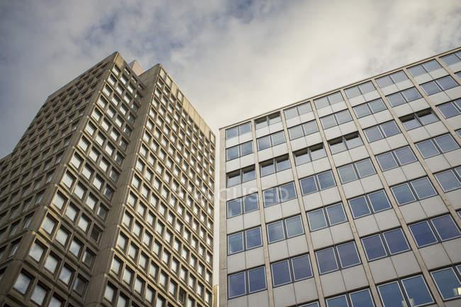 Vue de dessous des immeubles de bureaux sous un ciel nuageux bleu — Photo de stock