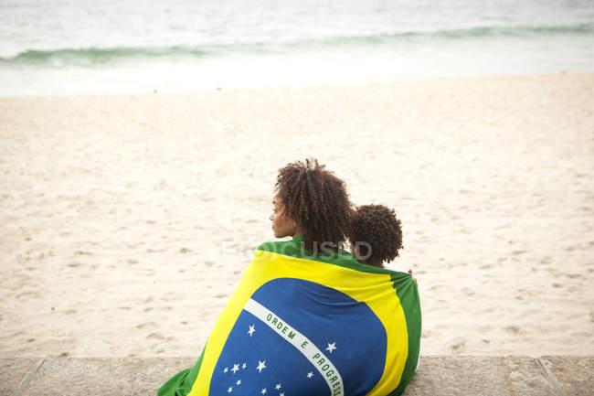 Вид сзади на молодых мать и сына, завернутых в бразильский флаг, с пляжа Ипанема, Рио-де-Жанейро, Бразилия — стоковое фото