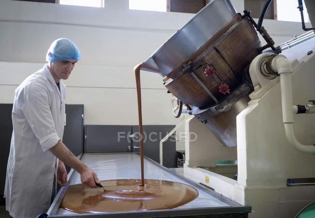 O trabalhador que espalha o Fudge do confeiteiro derramou na fábrica do chocolate — Fotografia de Stock