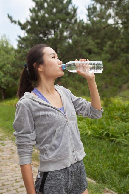 Молодая бегунья пьет бутилированную воду в парке — стоковое фото