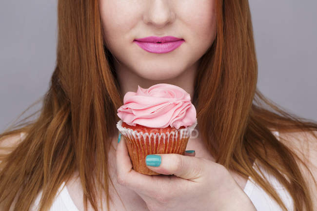 Cropped image of young woman holding cupcake — Stock Photo