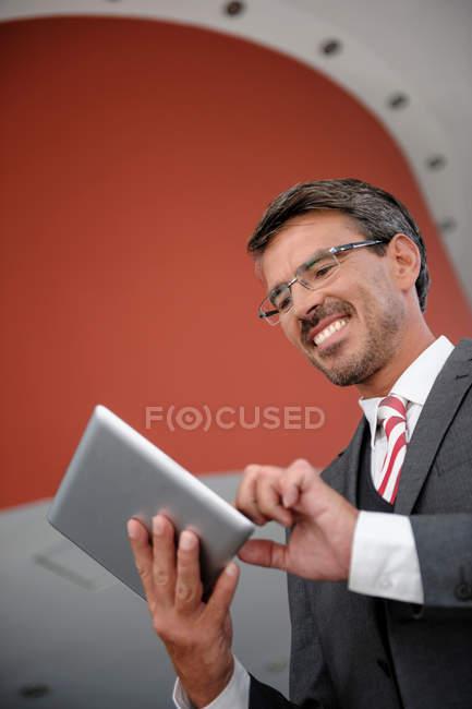 Homme d'affaires souriant regardant tablette numérique — Photo de stock