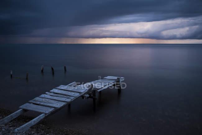 Tir longue exposition de jetée sur la plage au coucher du soleil — Photo de stock