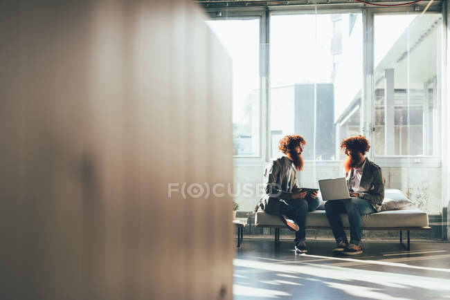 Male adult hipster twins sitting whilst working on laptop in office — Stock Photo