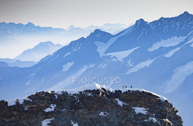 Paysage de montagnes aux sommets enneigés des randonneurs éloignés sur pic — Photo de stock