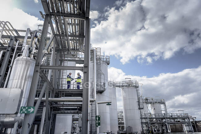 Workers on top of process plant in oil blending factory, low angle view — Stock Photo