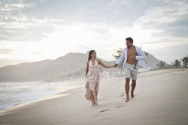Casal adulto médio andando ao longo da praia, de mãos dadas — Fotografia de Stock