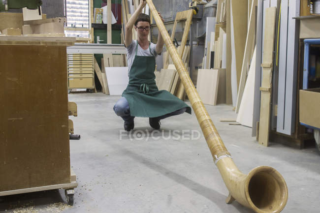 Woman in workshop checking alphorn — Stock Photo