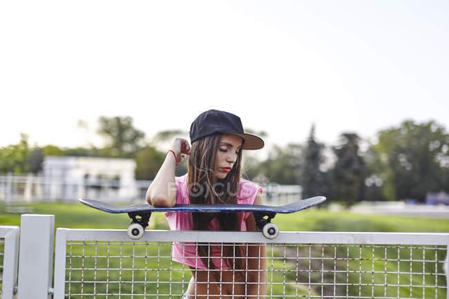 Jovem mulher balanceamento de skate na cerca de metal, cotovelo em skate — Fotografia de Stock