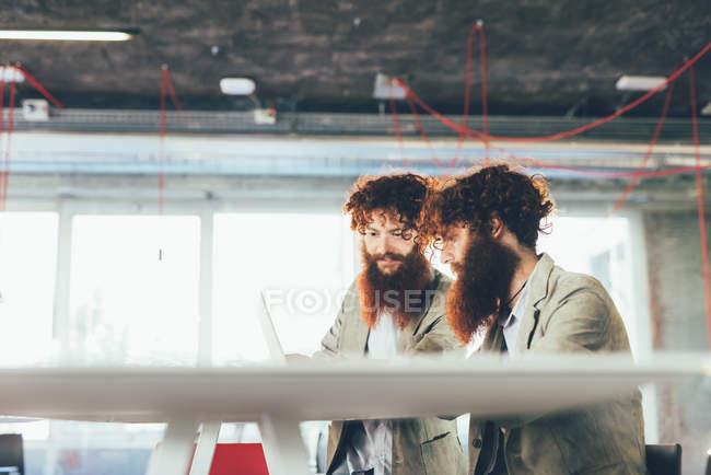 Gemelos hipster masculinos trabajando en portátil en el escritorio de la oficina - foto de stock