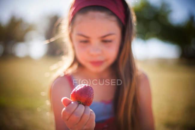 Девушка ест клубнику на открытом воздухе — стоковое фото