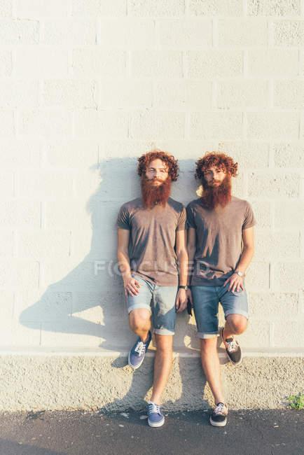 Портрет идентичные близнецы взрослых мужчин с рыжими волосами и бородки белые стены — стоковое фото