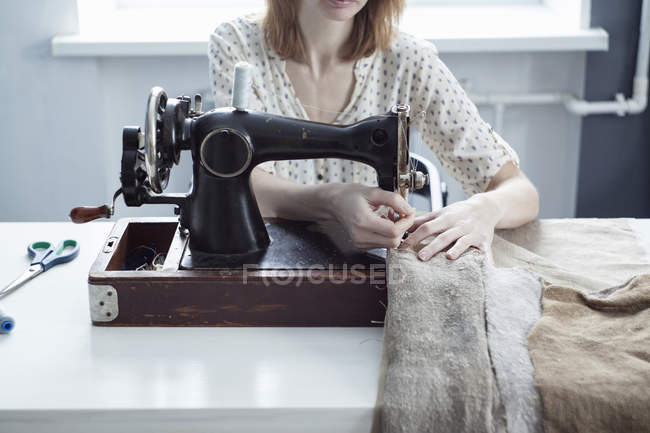 Cropped view of woman sewing textiles on vintage sewing machine — Stock Photo