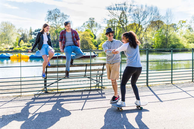 Young woman with friends learning to skateboard on lakeside in Battersea Park — Stock Photo